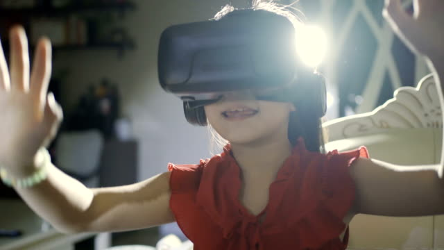 little girl using a virtual reality glasses at home - curiosity stock videos & royalty-free footage