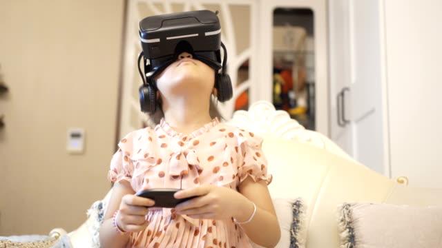vídeos de stock e filmes b-roll de little girl using a virtual reality glasses at home - homem e máquina