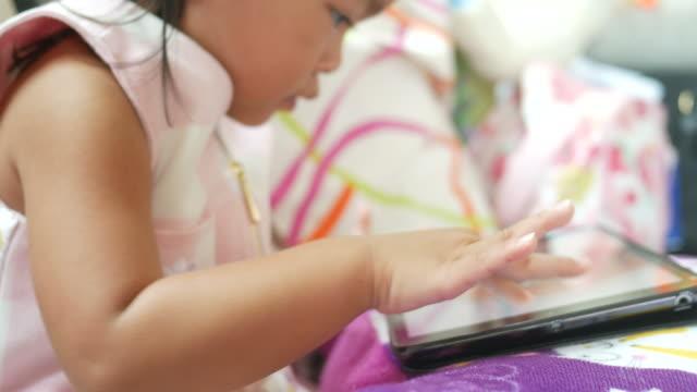 bambina che usa tablet digitale - curiosità video stock e b–roll
