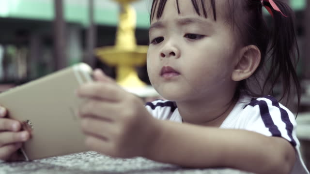 CU:Little girl using digital tablet