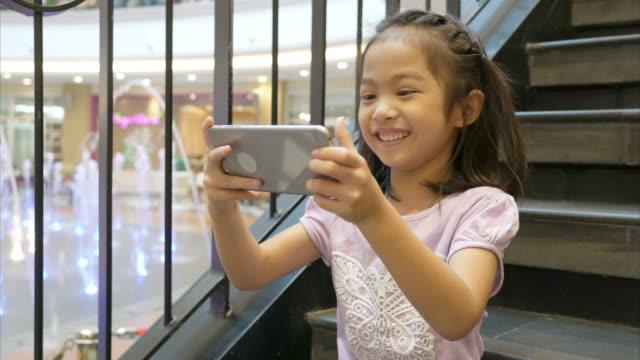 kleines mädchen mit telefon für webcam auf treppe - little girl webcam stock-videos und b-roll-filmmaterial
