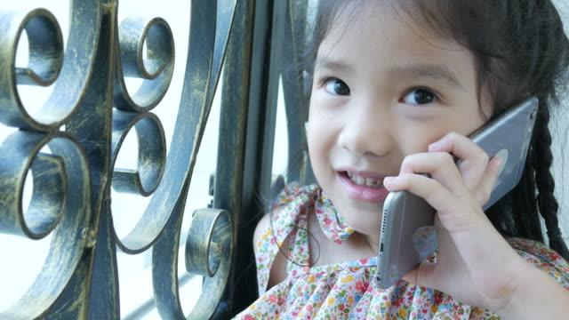 Petite fille à l'aide de téléphone près de fenêtre