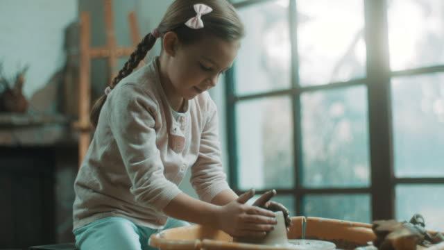 kleines mädchen mit töpferscheibe im atelier - kind vor der pubertät stock-videos und b-roll-filmmaterial