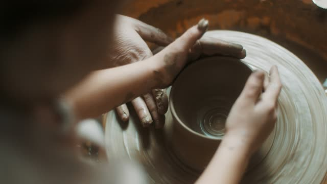 little girl using pottery wheel at atelier - prodotti in ceramica video stock e b–roll
