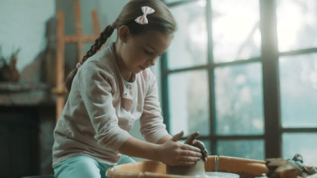 vídeos de stock e filmes b-roll de little girl using pottery wheel at atelier - ceramista