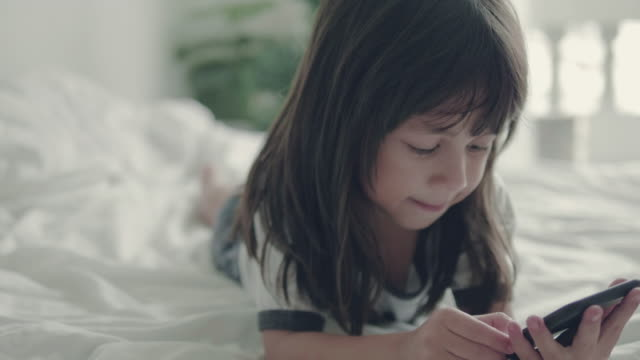 Little girl (5 years) using smart phone at home