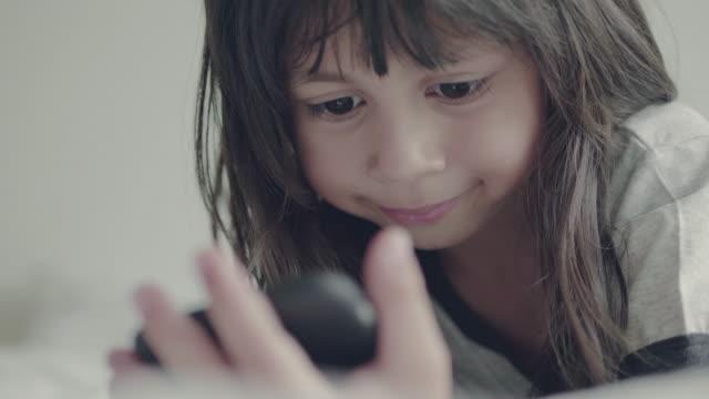 liten flicka (5 år) använder smarta telefonen hemma - barndom bildbanksvideor och videomaterial från bakom kulisserna