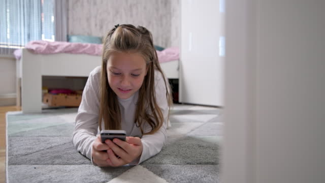 little girl using smart phone in her room - carpet stock videos & royalty-free footage