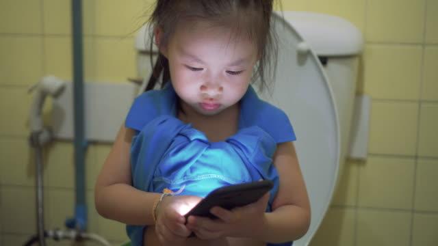 kleines mädchen mit smartphone in der toilette - kind pinkelt stock-videos und b-roll-filmmaterial