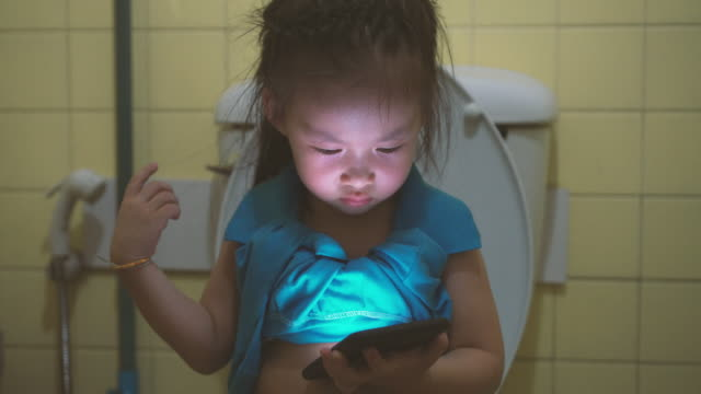 little girl using smart phone in toilet - real life stock videos & royalty-free footage