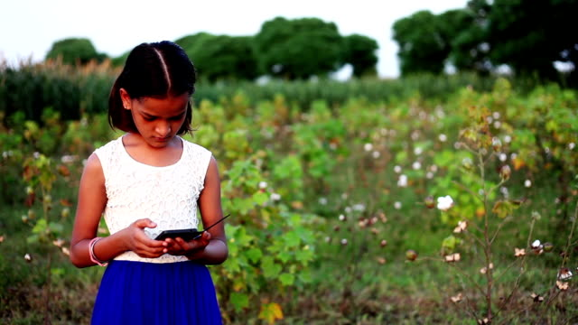 Little girl using smartphone outdoor in the field
