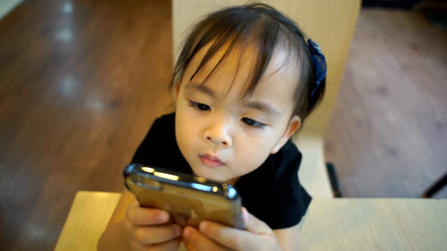 Little girl using tablet in restaurant
