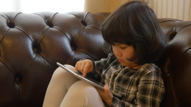 Little girl using tablet on sofa moving slider right to left