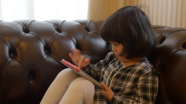 little girl using tablet on sofa - タブレット使用点の映像素材/bロール
