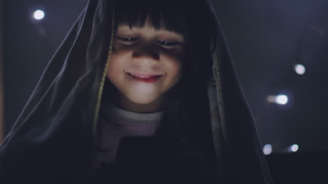 Little girl using tablet under the blanket on the bed