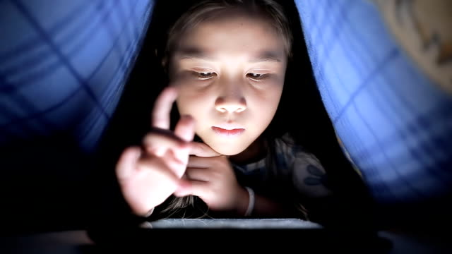 stockvideo's en b-roll-footage met little girl using tablet under the blanket - person in education