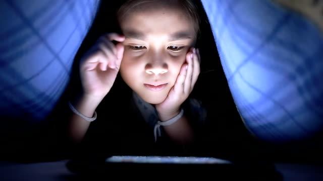 vidéos et rushes de petite fille à l'aide de tablettes sous la couverture - synthpop