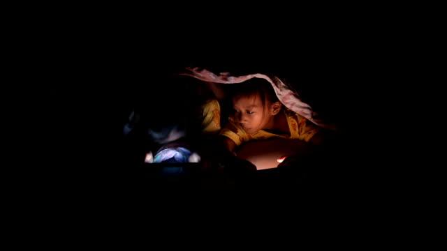 Rapariga com o comprimido sob o Cobertor