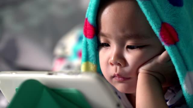 stockvideo's en b-roll-footage met meisje met behulp van de tablet onder de deken - elektronische organiser