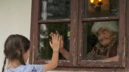 Little Girl Visits Grandmother during Pandemic Through Window