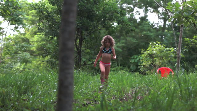 ms tu little girl walking in meadow towards with a lime in her hand / cobano, puntarenas, costa rica - kelly mason videos stock-videos und b-roll-filmmaterial
