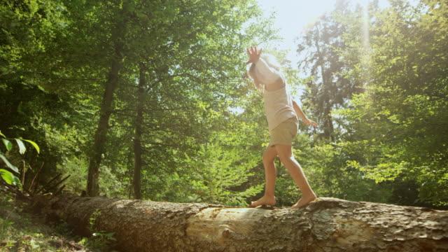 vídeos y material grabado en eventos de stock de slo mo ts niña caminando sobre un tronco de árbol caído en el bosque soleado - equilibrio