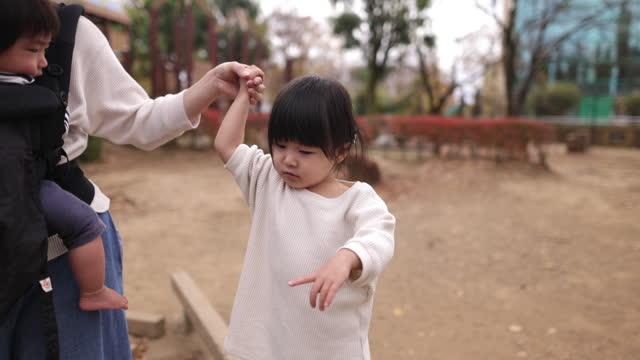 vidéos et rushes de petite fille marchant sur la poutre d'équilibre avec l'aide de sa mère dans le stationnement public - partie 1 de 2 - son