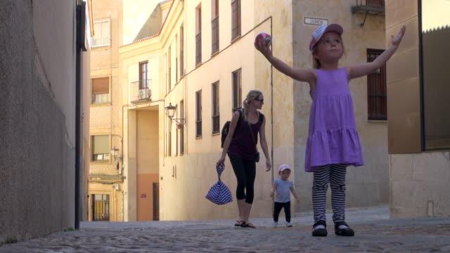 vídeos de stock, filmes e b-roll de little girl walking through narrow cobbled streets - objeto manufaturado