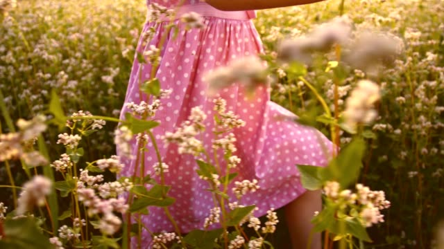 SLO MO Little girl walking through the buckwheat field