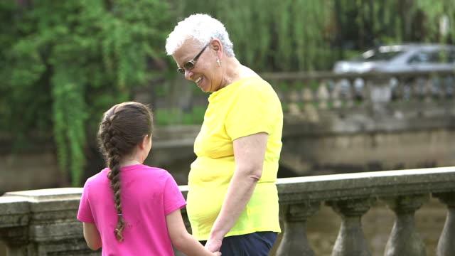 vídeos y material grabado en eventos de stock de niña caminando con la abuela en el parque - 65 69 años