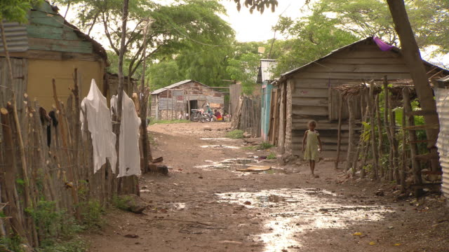 a little girl walks past shacks in a village. - hispaniola stock videos & royalty-free footage