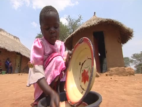 A little girl washes a plate Zambia