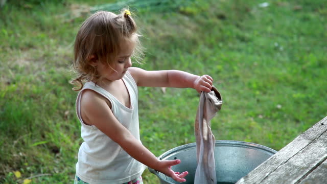 little girl washing a dirty sock in the metal basins - adult imitation stock videos and b-roll footage