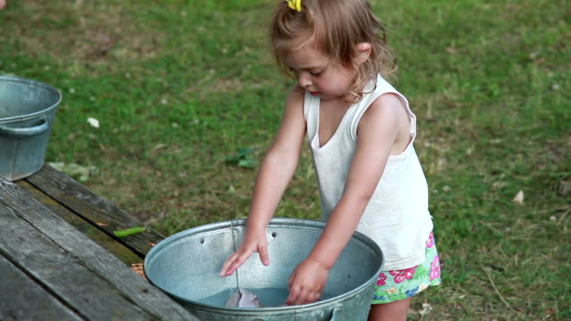 little girl washing dirty socks in the metal basin - adult imitation stock videos and b-roll footage