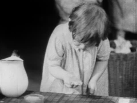 b/w 1934 little girl washing hands at nursery school / wpa project / newsreel - ein mädchen allein stock-videos und b-roll-filmmaterial