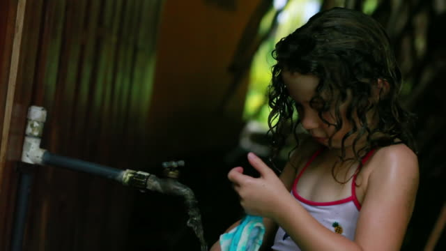 stockvideo's en b-roll-footage met ms little girl washing sand off her body and bathing suit under outside tap / montezuma, puntarenas, costa rica - alleen kinderen