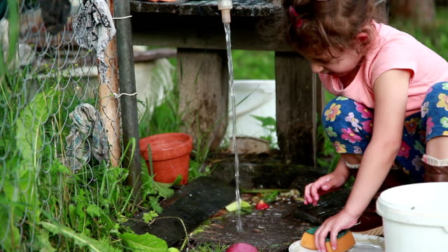 little girl washing the dishes under faucet in the backyard - adult imitation stock videos and b-roll footage