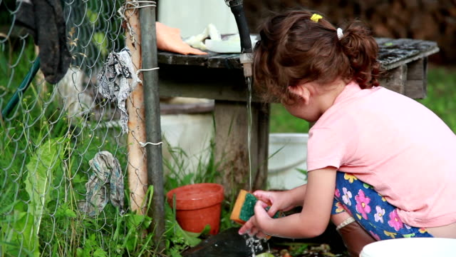 little girl washing the dishes under the garden tap in the backyard - adult imitation stock videos and b-roll footage