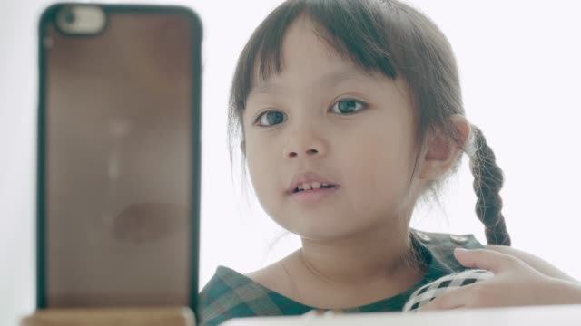 little girl watching cartoon in smartphone for her leisure activities at home - technophile stock videos & royalty-free footage