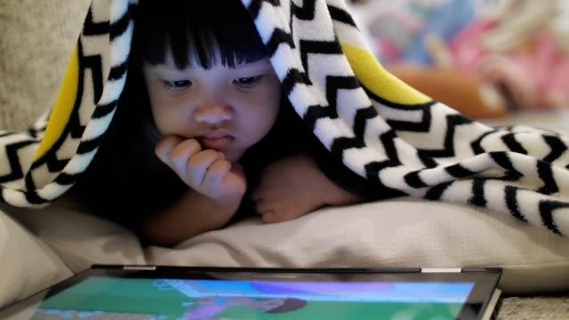 vídeos de stock, filmes e b-roll de câmera lenta: menina assistindo mídia de entretenimento na tabuleta à noite antes de dormir - agenda eletrônica