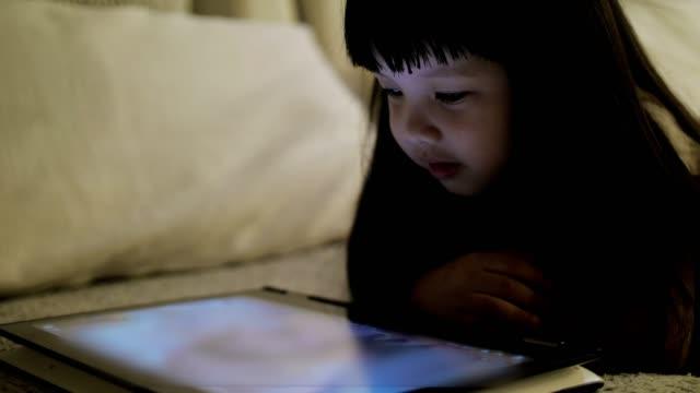 vídeos y material grabado en eventos de stock de slow motion: pequeña niña viendo medios de entretenimiento en la tableta en la noche antes del sueño - música pop