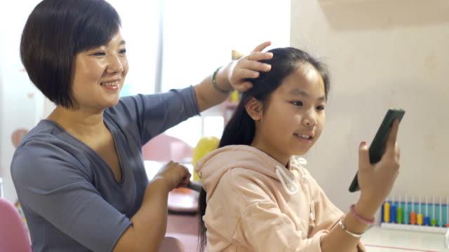 母が彼女の髪をコーミングするとき携帯電話を見ている小さな女の子 - 髪をブラシでとく点の映像素材/bロール