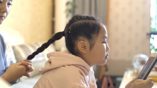 母が彼女の髪をコーミングするときにタブレットコンピュータを見ている小さな女の子 - 髪をブラシでとく点の映像素材/bロール