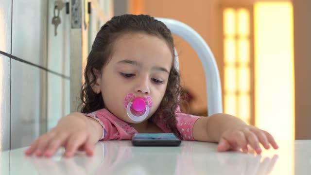 kleines mädchen, das video auf dem handy anschaut - pureza stock-videos und b-roll-filmmaterial
