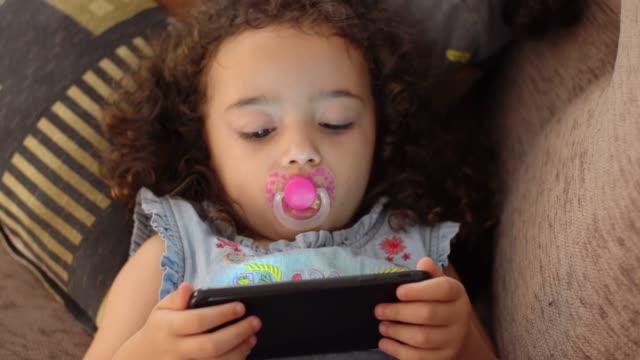 vídeos de stock, filmes e b-roll de menina assistindo vídeo no smartphone - criança pequena