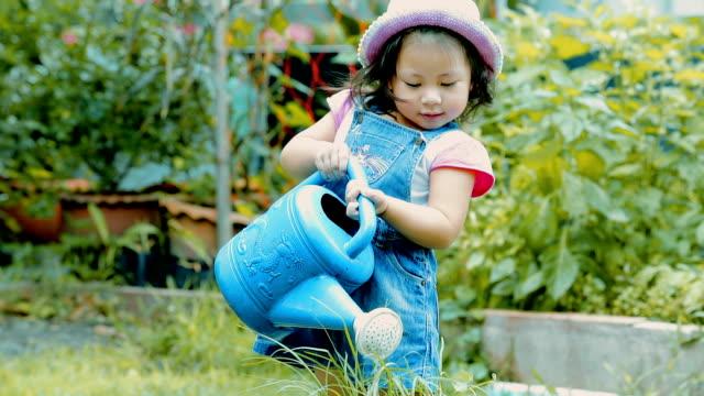 stockvideo's en b-roll-footage met klein meisje drenken plant in tuin \ \ concept: het verzorgen van de natuur - gieter