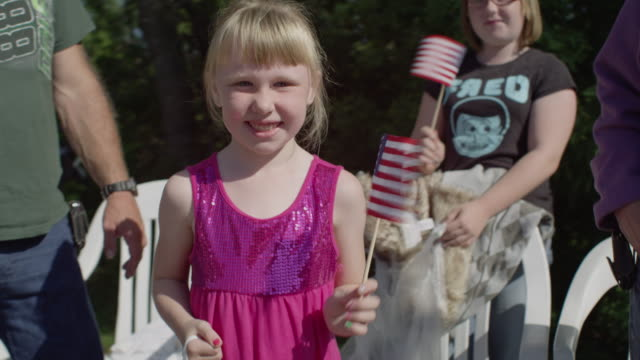 Little girl waves a small USA flag while watching a small town parade.