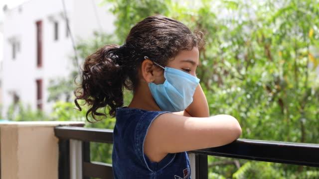 stockvideo's en b-roll-footage met meisje dat een gezichtsmasker draagt en uit van balkon gluurt - gluren