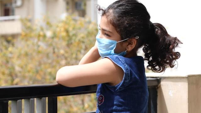 vídeos de stock, filmes e b-roll de menina usando uma máscara facial e espiando para fora da varanda - máscara cirúrgica