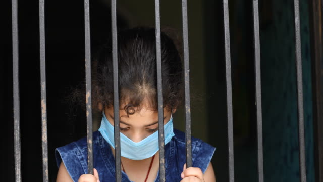little girl wearing a face mask and peeking out from window - sadness stock videos & royalty-free footage